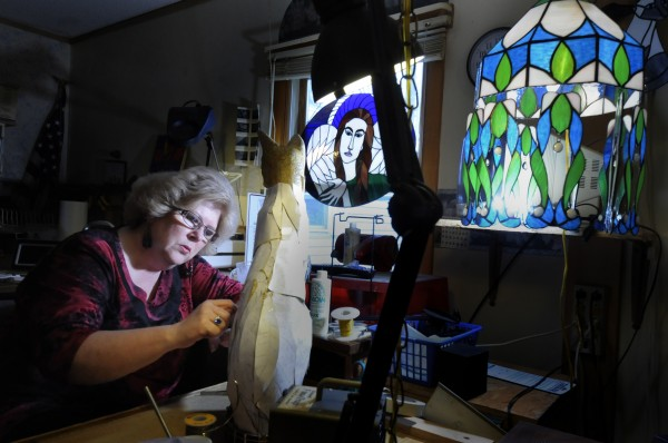 Surrounded by her tools and her art, Amber Martin works on one of her latest creations, a stained-glass Egyptian cat.