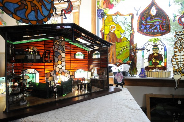 Amber Martin's award-winning stained-glass cabin, foreground, is on display with her other colorful stained-glass works in her studio in Milford on April 27, 2011. Her 3-D stained-glass cabin won second place in the International Delphi Online Art Glass Festival competition.