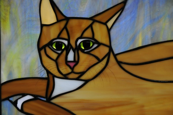 Artist Amber Martin made a stained-glass renditon of one of her dearly departed cats, Suqee, which hangs in the sun room of her home in Milford.