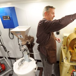 Jeff Savage of the Savage & Sons Gourmet Coffee dumps some raw coffee beans into the roaster at his home in Bangor.  Savage started the business in November of last year and currently produces three kinds of fresh roasted coffee.