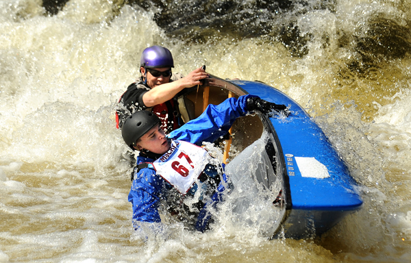 Dylan Carter (foreground) and Dan Cohnstaedt capsize at the drop at the Emerson Mill Road bridge during the 36th annual Souadabscook Stream Race in Hampden Saturday. Cohustaedt is the principal and Carter is a junior at Calais High School.  They ran the race in preparation for the Kenduskeg that is next weekend.