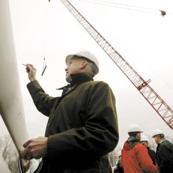 Paul Gaynor, CEO of Massachusetts-based First Wind, signs one of the windmill blades at the Stetson II wind project expansion in Township 8 Range 4 near Danforth.