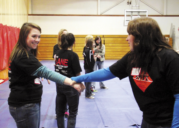 Lydia Kieffer (left), and Jessica Zbylut, practice self-defense techniques during the Totally Trades Day at Northern Maine Community College on Wednesday. Approximately 100 girls gathered at NMCC during the day for the Totally Trades Conference, an event geared toward generating interest among girls in occupations that primarily are dominated by men.