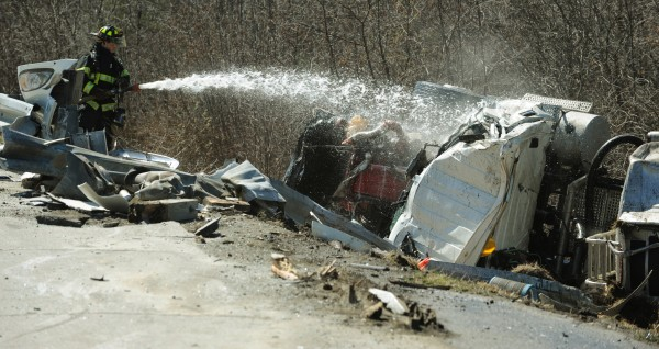 A Bangor firefighter sprays foam on the wreckage of an R.H. Fosters semi tanker that rolled over on the Route 202 westbound on ramp from I-395 on Friday, April 15, 2011. The Orono/Old Town hazmat team was on scene to handle the spilled fuel oil.