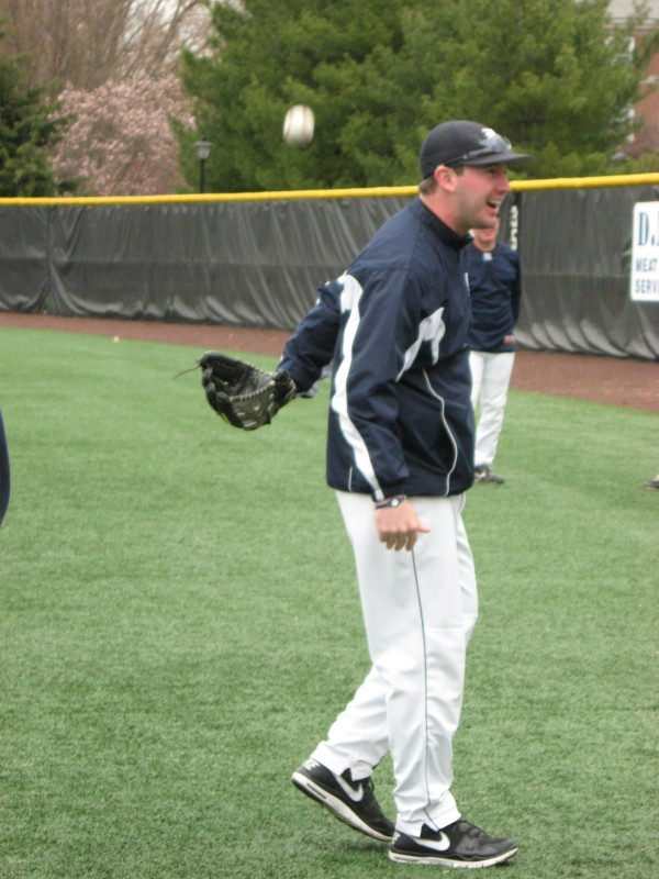 University of Maine assistant coach Billy Cather catches the ball behind his back as the Black Bears loosen up prior to Sunday's doubleheader in New York.
