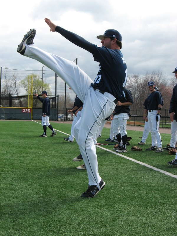 University of Maine senior co-captain Joe Miller gets stretched out with some high-leg kicks prior to Sunday's America East baseball game at West Hartford, Conn.
