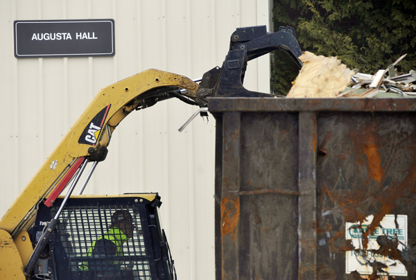 A worker moves debris to a dumpster from the soon-to-be-razed Augusta Hall on the campus of the newly-named University of Maine at Augusta Bangor campus. Last month University College of Bangor officially changed its name to UMA Bangor. The Augusta Hall demolition will make way for a new outdoor meeting place on campus.