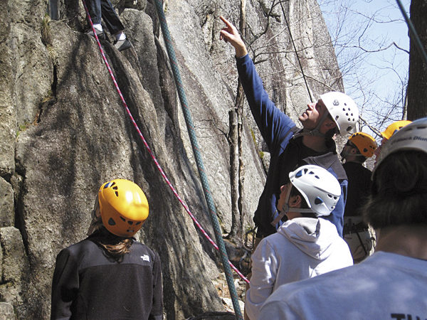 Scott Fraser points out a climbing hold to a student whose feet are just visible in the top left of the frame. Fraser, the faculty of the Adventure Recreation and Tourism program at Washington County Community College, led nine students on a four-day climbing course.