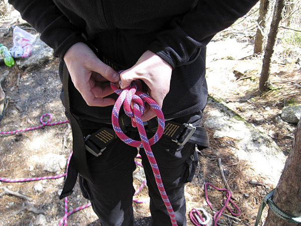 Lisa Leighton ties in to her climbing harness before climbing the rock face at Eagle Bluff.