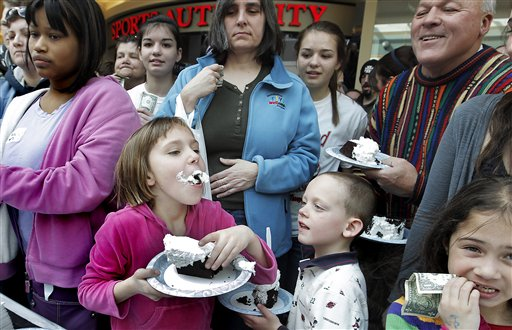 As brother Ryan, 6, lower right, looks on, Natalie Grondin, 9, of Falmouth, Maine, facing center, is one of the first to get a taste of the 1000-plus pound Whoopie Pie that was put together at the Maine Mall in South Portland, Maine, Saturday, March 26, 2011. On Tuesday, the House passed a bill making the whoopie pie the state's official treat.