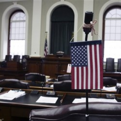 A flag hangs on the microphone of  a Legislator's desk in the House chambers at the State House in Augusta, Maine, on Monday, April  4, 2011.  Rep. Linda Valentino, D-Saco,  wants to make Maine the second state with a unicameral Legislature. (AP Photo/Pat Wellenbach)