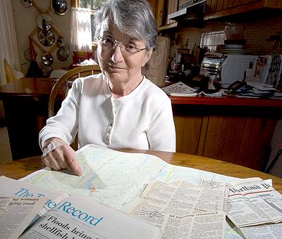 Ann Baribeau of Brunswick, sitting at her kitchen table amid 18-year-old newspaper clippings chronicling the story of her rescue, points on a map to where she was stuck in her car for three days.