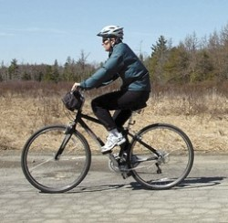 A cyclist pedals down University Farm Road on Tuesday. Lawmakers in Augusta are currently considering a new law which aims to tax all bicycles sold in Maine, with revenues benefiting improved biking thoroughfares.