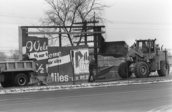 A billboard on Main Street in Bangor is torn down by Maine Department of Transportation workers in January 1984.
