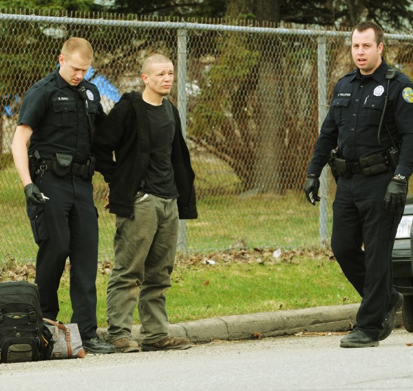 Bangor Police officer B. Smith (left) handcuffs Phillip Smith in an alleged mugging on Buck Street on Monday, April 18, 2011 as Officer S. Pelletier (right) calms an irate female (not pictured) who was later released at the scene.