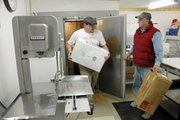 Errol Libby Jr. carries a box of meat from his walk-in refrigerator as his father, Errol Sr., talks as they prepare to open the family's Lincoln Lakes Olde Tyme Butcher Shoppe in Lincoln on Thursday.
