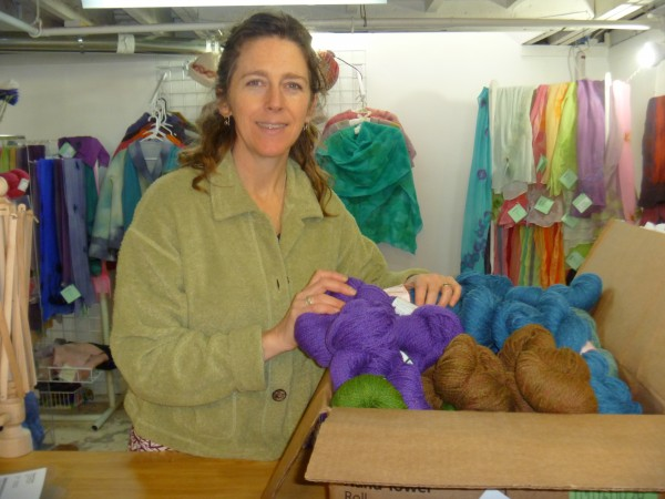 Jodi Clayton, owner of One Lupine in Bangor, unpacks a box of Peace Fleece yarn in the studio area of her newly expanded business which now offers space where knitters and fiber artists can gather to share their interests.