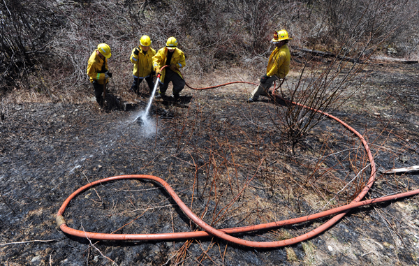 Firefighters from Carmel, Etna and Levant work together to put out hot spots along railroad tracks near the town of Carmel's recreation fields on Tuesday.
