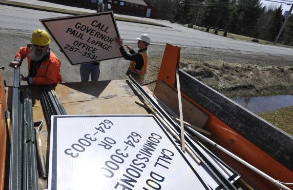 Carmel transportation department workers Bryan Hodgkins (from left), Willie Dunton and Thomas Benecke removed four signs that Carmel town manager Tom Richmond put up along Route 2 in Carmel to encourage residents to petition Gov. LePage and the DOT commissioner for road improvements there. On Wednesday, Gov. LePage will announce his road work priorities for the next biennium. Included on the list is Route 2 in Carmel. Photographed April 12, 2011 across from Ye Ole General Store in Carmel.