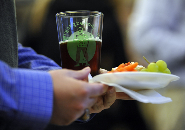 An attendee holds healthy food offerings and a complimentary pint glass with Bangor's Greendrinks logo during the Greendrinks gathering at the offices of WBRC Architects-Engineers in downtown Bangor in March. The recently-started Bangor Greendrinks movement joins a worldwide network of other Greendrinks informal social networking events which are geared towards enviromental and sustainable values.