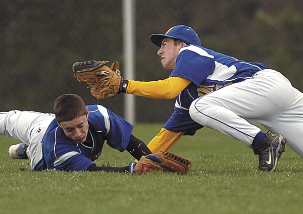 Hermon's Dylan Smith, right, catches a fly ball as teammate Tyler Fournier dives to provide backup as Hermon hosted Bucksport on Saturday.