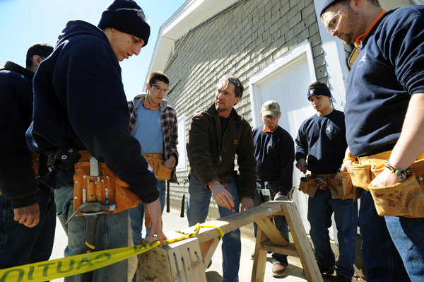 Mark Martin (center), instructor at the Home Builders Institute on the Penobscot Job Corp campus draws a sketch on a saw horse to show his students the next step in laying out a building in the parking lot of the center on Thursday.