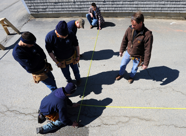 Mark Martin (right), instructor at the Home Builders Institute on the Penobscot Job Corp campus watches as his students apply the math skills he taught them earlier as they use tape measures and a chalk line to mock up a building layout in the parking lot of the center on Thursday.