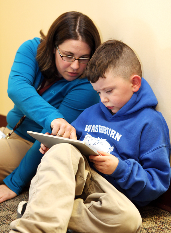 Kindergartener Lucius Rice, 6, right, and literacy teacher Maurie Dufour, left, look at a book on an iPad Tuesday, April 12, 2011 in Auburn, Maine. Five teachers were given iPads to try out in preparation for next year when nearly 300 kindergartners will be given their own iPad2s