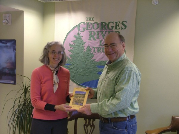 """Linda Arnold, administrative assistant at Georges River Land Trust presents Jim Parker of South Thomaston a copy of """"Best Nature Sites: Midcoast Maine"""" by Kyrill """"Buzz"""" Schabert and Tony Oppersdorff. Parker was the lucky winner of the book in a drawing conducted by the land trust recently."""