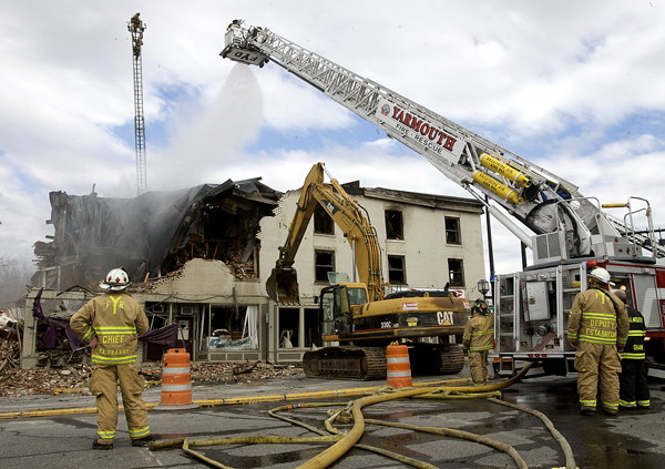 Firefighters from several town keep an eye on a building at the corner of Maine and Mason Streets in Brunswick Sunday as it is torn down for safety reasons after it burned in the early morning hours.
