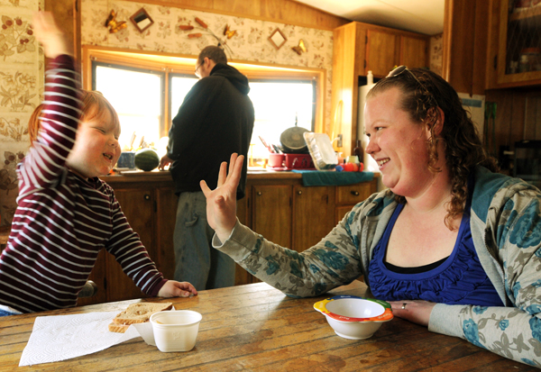 Gabriel Baker (left), plays with his mother Nicole as his father prepares lunch at the familys trailer in Machiasport on Friday. The Baker family is together today due to policy changes at the Department of Health and Human Services.