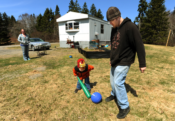 The Baker family of Machiasport, Nicole (left), Gabriel (center) and Nathaniel, (right) play ball outside their rented trailer on Friday. The Baker family is together today due to policy changes at the Department of Health and Human Services.