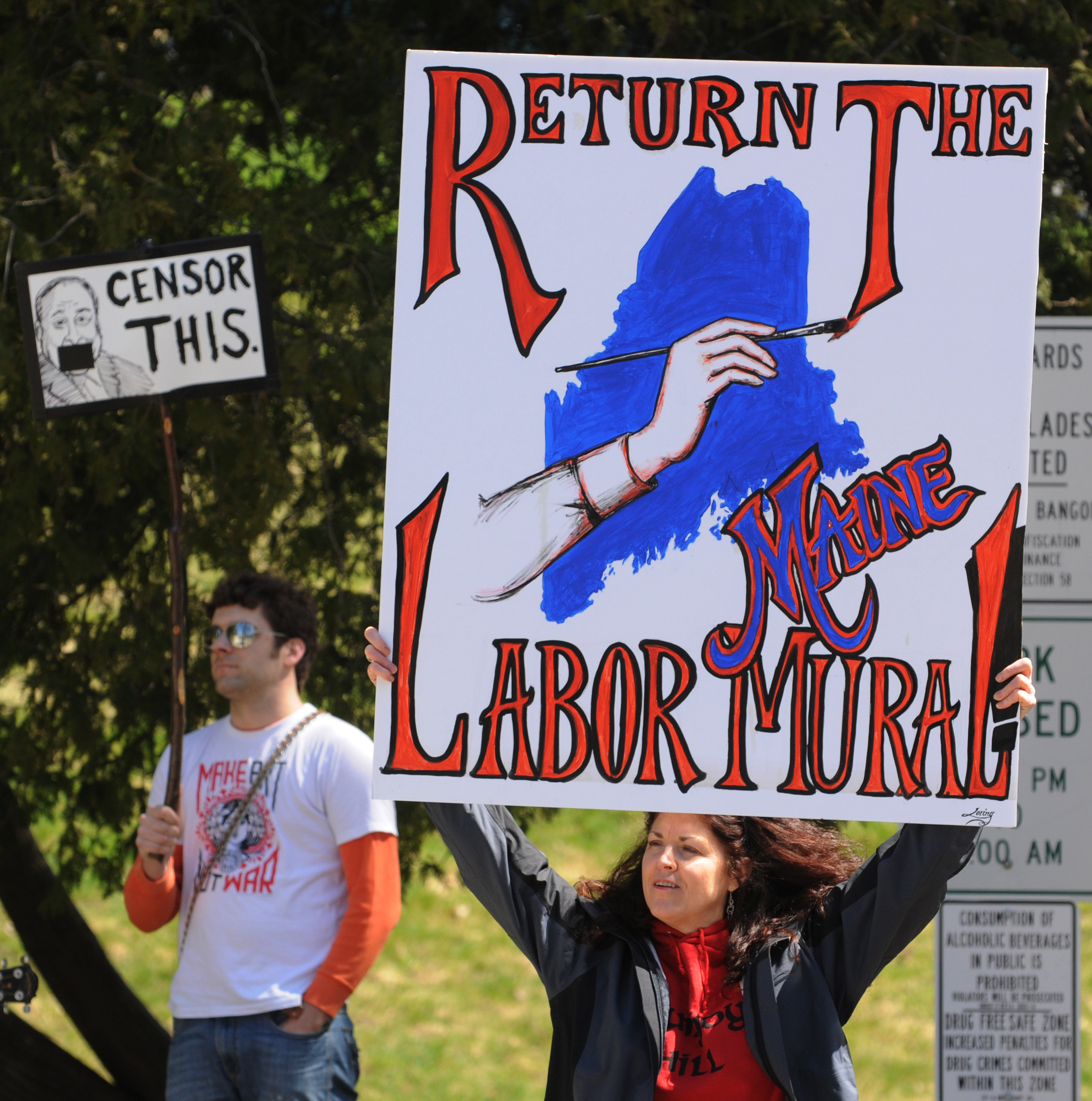 A woman holds a sign supporting the return of Judy Taylor's  History of Maine Labor mural during a rally at Pierce Park in Bangor on Tuesday.