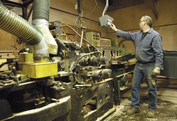 Glenn Tarr of New Limerick works at a four-sided planer at Katahdin Cedar Log Homes of Oakfield in 2009.