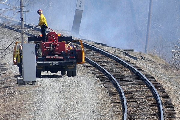 A firefighter douses one of several brush fires along a railroad track near Route 2 in Carmel early Tuesday afternoon. Several fire departments, including Carmel and Newburgh, responded.