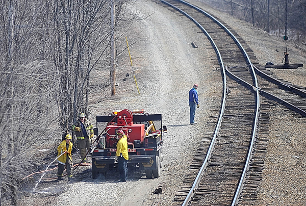 Firefighters douse one of several brush fires along a railroad track near Route 2 in Carmel early Tuesday afternoon. Several fire departments, including Carmel and Newburgh, responded.