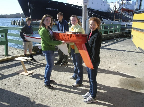Jessie Sweeney (from left), Mikala Leland and Mariah Dennis, all seventh-grade students at the Reeds Brook Middle School in Hampden, deliver a small sailboat to Maine Maritime Academy on Friday as part of the Educational Passages program they are participating in. Sudents at three schools in Maine and one in Connecticut have worked on the boats since last fall and will track them using GPS technology after they are launched by MMA students on the State of Maine during the ship's annual training cruise, which starts next month.