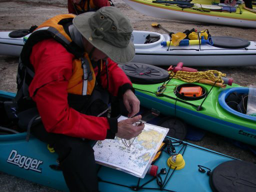 A kayaker uses his compass and chart to plot a course from Steves Island in the Stonington area.