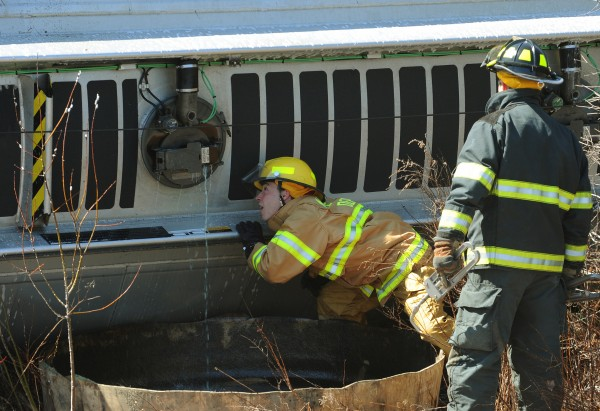 A Maine Department of Enviromental Protection worker checks his work on a fuel hatch on an R.H. Foster fuel tanker after it rolled over on the 202 onramp from I- 395 westbound on Friday, April 11, 2011.