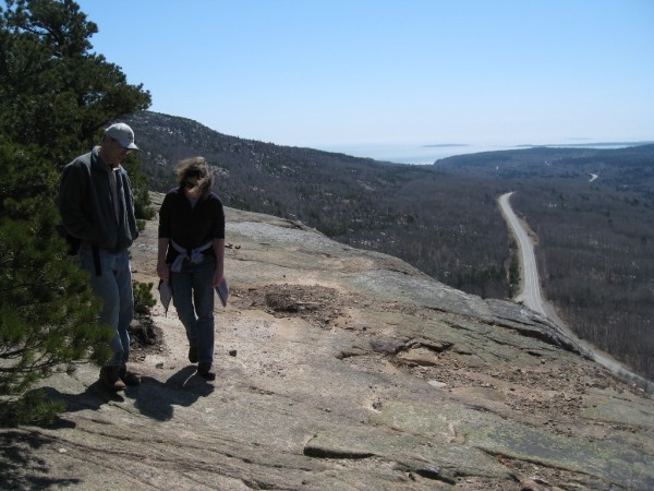 Steve McKay and Cathy Anderson of Orono hike along the open ledge on the Beachcroft Trail. Route 3 to Otter Creek is the road at the base of the mountain.