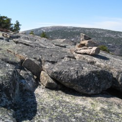 Cairns like this one mark the trail near the summit of Champlain Mountain. Cadillac Mountain rises in the distance in the view from the Bear Brook Trail.