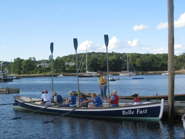 "Participants prepare for a community row in the Cornish gig ""Belle Fast."""