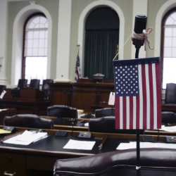 A flag hangs on the microphone of a legislator's desk in April. A legislative committee on Monday rejected three bills that would reduce the size of the Legislature.