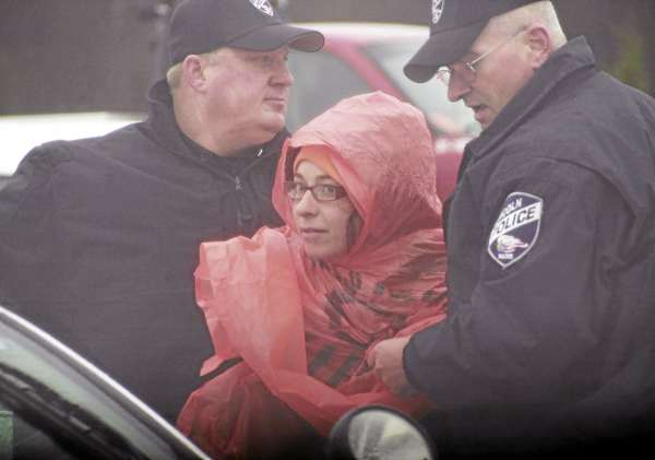 Two Lincoln police officers take Jessica Dowling, 29, into custody during a public protest of the construction of 40 1.5-megawatt wind turbines on Rollins Mountain in Lincoln in Nov. 2010.