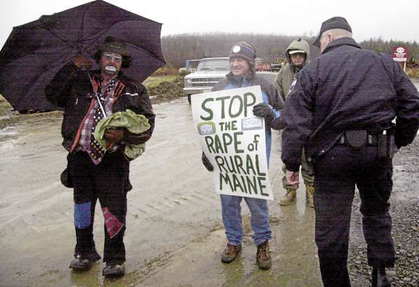 Brad Blake (center) holds a sign in protest of the $130 million Rollins Mountain industrial wind site in Lincoln as a police officer (right) moves toward him. A Cape Elizabeth resident who owns a cabin and property in Lincoln, Blake is spokesman for the Citizens Task Force on Wind Power, an umbrella group of 14 anti-windmill groups in Maine.