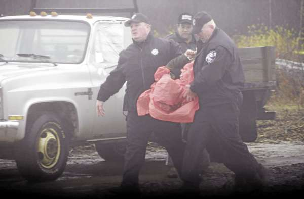 Three police officers take one of three protestors into custody at the $130 million Rollins Mountain industrial wind site off Route 6 in Lincolnin Nov. 2010.