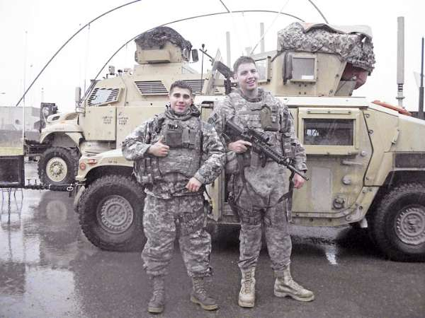 Army Reserve Spc. David T. Aston (left)  of Bangor returned home from Iraq on Tuesday with the  94th Military Police Company, based in Saco. At right is fellow reservist Ryan Campbell.  The unit, which includes 42 Mainers, spent 10 months training Iraqi police.
