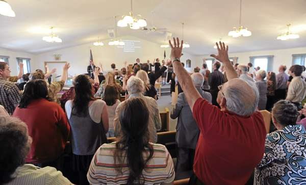 "Jimmy Holmes (right) raises both hands heavenward on Sunday as he joins other Calvary Apostolic Church members on the first service being held at the Winterport Baptist Church after Wilbur ""Wes"" Strout ingnited a fire at the Calvary Apostolic Church on Route 1A in Winterport on Thursday, May 5, 2011, that killed him and destroyed the building."