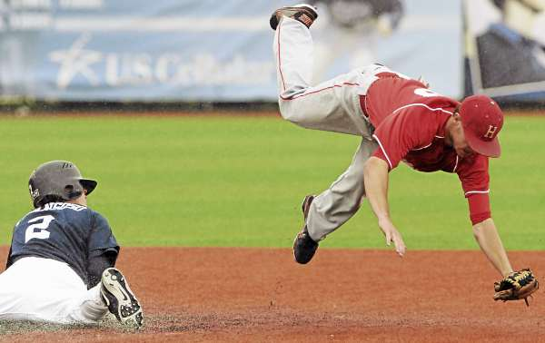 Hartford's Simon Kudernatsch trips while attempting to field a throw as UMaine's Michael Fransoso steals second base in seventh-inning action at Mahaney Diamond in Orono Sunday. Maine won 3-2 in 10 innings.