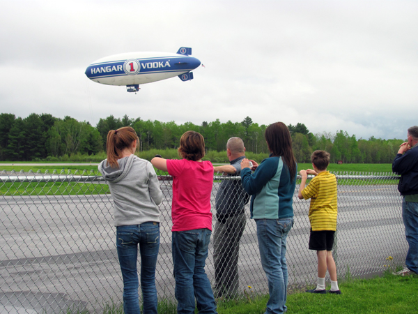 A blimp bearing an advertisement for Hangar 1 Vodka caused a stir Friday evening, May 20, 2011, when it touched down at Pittsfield Municipal Airport in an effort to avoid a thick cloud cover and rain in the forecast. Dozens of area residents, some of whom followed the airship to Pittsfield after seeing it in the air further north, gathered on the tarmac for one of the more interesting aerial spectacles the town has seen in quite some time.